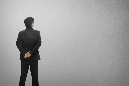 Standing business man and blank wall for text and background. Foto de archivo