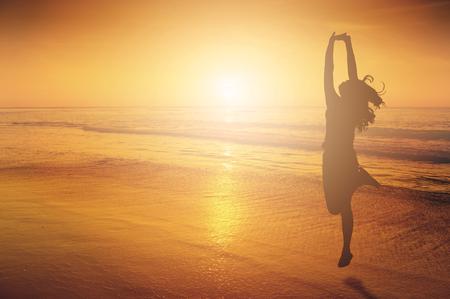 bewegung menschen: Glückliche Frau Springen auf Meer Strand bei Sonnenuntergang Silhouette. Lizenzfreie Bilder