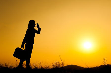 Business woman shout and holding bag at sunset silhouette.Copy Space