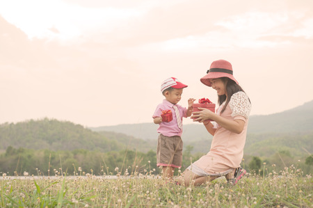 A mother and son giving gift box on outdoors