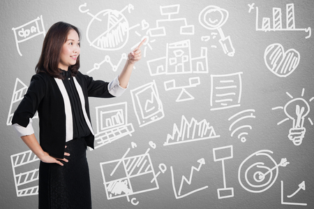 Businesswoman smiling pointing  at business concept chart graph on wall background