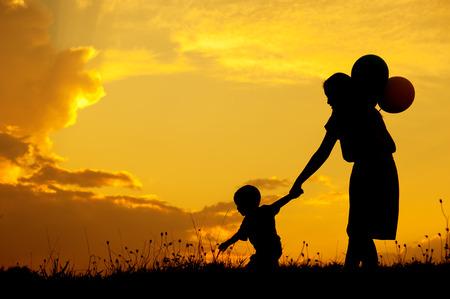 silueta humana: Silueta de una madre y su hijo que juegan al aire libre en la puesta del sol Foto de archivo