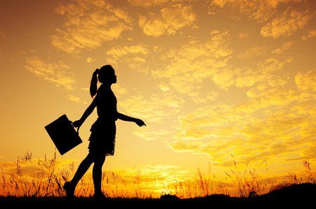 Business woman standing and sunset silhouette
