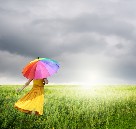 Beautiful woman holding multicolored umbrella in Yellow field and rainclouds