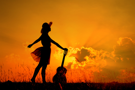 Woman and guitar with sunset silhouette