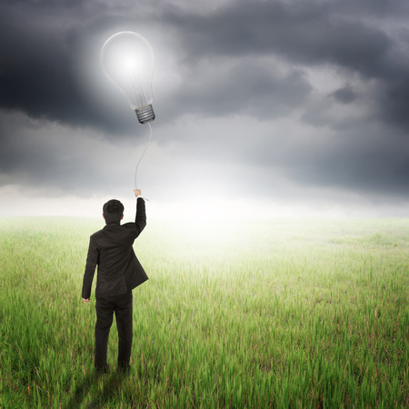 Business man holding bulb balloon in fields and raincloud