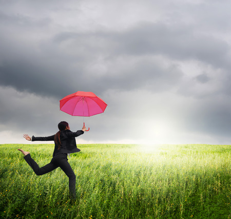 Business umbrella woman jumping to rainclouds in grassland with red umbrella