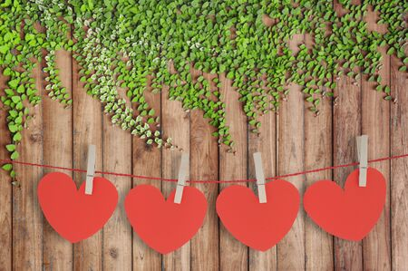 Red paper heart hanging on the clothesline on wood wall Foto de archivo