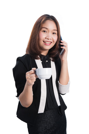 Asia businesswoman on phone and holding cup on white background Foto de archivo