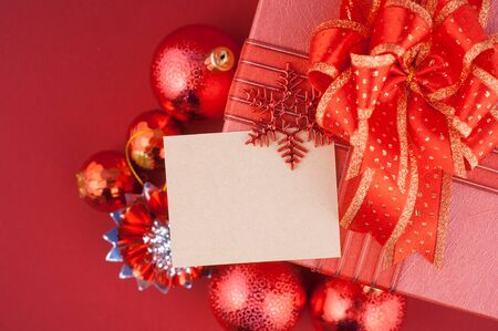 Christmas gift box with decorations and card on red background Foto de archivo