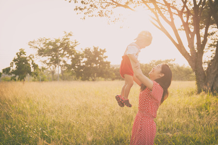 A mother and son playing in grass fields outdoors at evening.Vintage Tone and copy space
