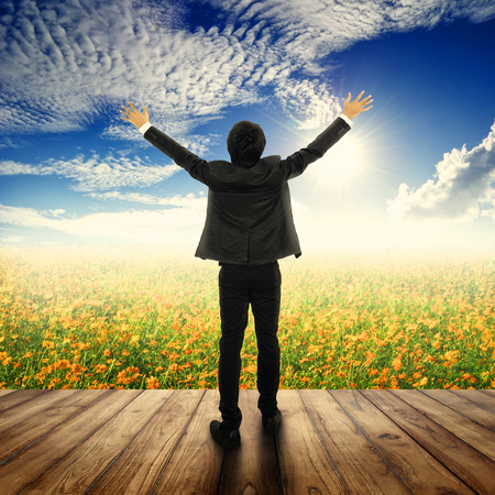 Happy business man standing on balcony and Yellow cosmos flowers and sun sky