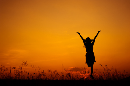 Happy woman jumping and sunset silhouette