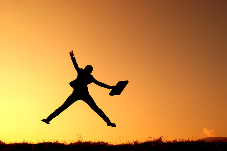 Business woman jumping and sunset silhouette Foto de archivo