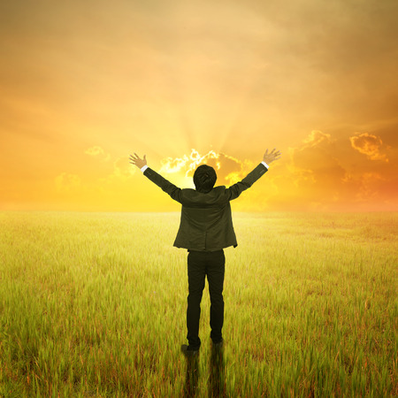 Happy Business Man standing to sunset in grassland