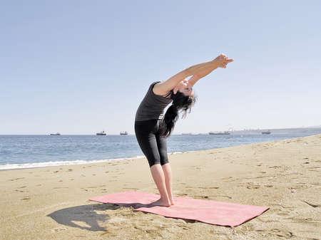 chandrasana: Yoga teacher practising at the beach pose arda chandrasana