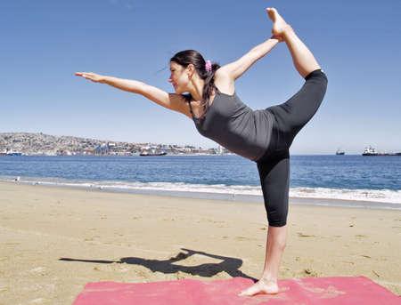 beach mat: Yoga teacher practising at the beach pose dandayamana dhanurasana Stock Photo