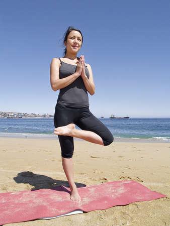 chandrasana: Yoga teacher practising at the beach pose tadasana