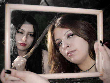 contemplates: A woman attacks with surprise another that contemplates herself on a mirror Stock Photo