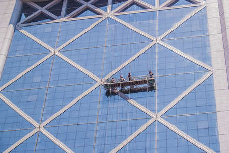 Santiago, February 2011. Professional workers clean the windows of an skyscraper from outside with a platform.