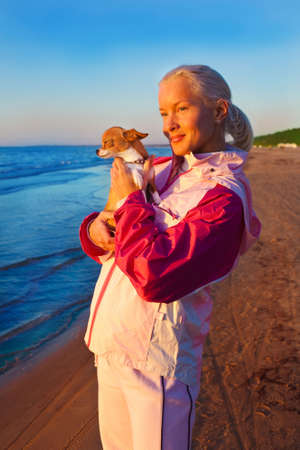 Young woman with her dog on a beach photo