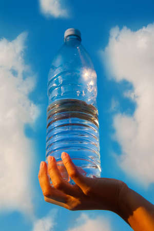 Human hand holding a bottle of water photo