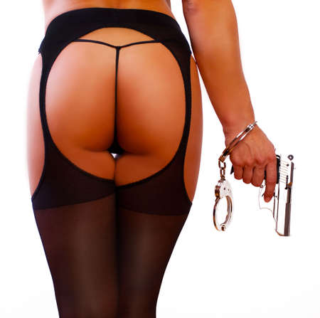 Young sexy girl with gun and handcuffs photo