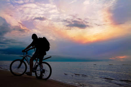 Mountain biker on beach and sunset, stormy sky  photo
