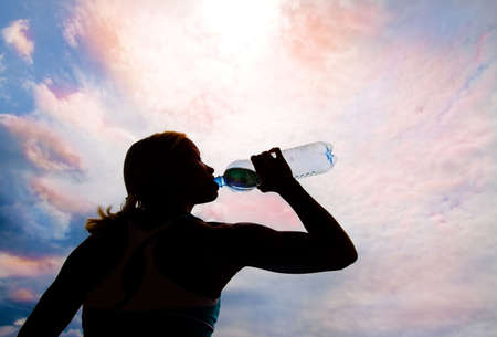 Beautiful young blond girl drinking water in the evening (sunset) photo