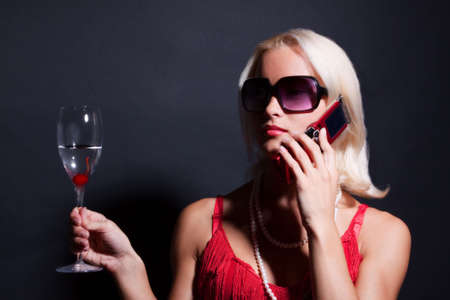 Attractive blond woman with phone and glass of martini Stock Photo - 5404162
