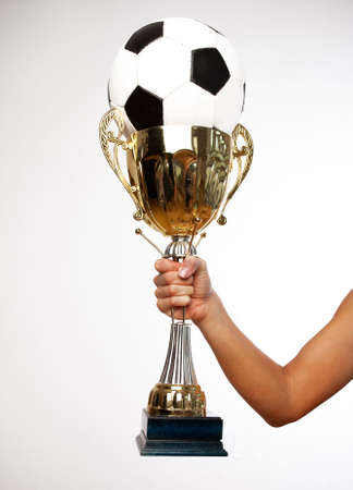 Portrait of hand holding winning cup with ball photo