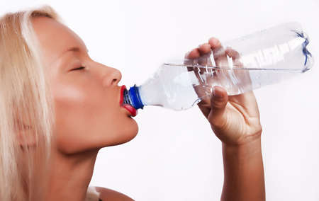 Beautiful young blond girl drinking water