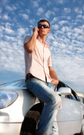 hot guy: Handsome man calling by cellular phone near his car