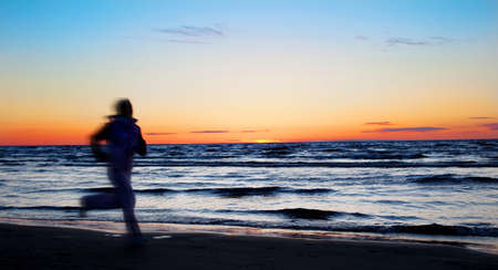 Young sportswoman running on the beach in the evening Stock Photo - 5442870