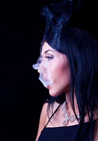 cigar smoking woman: Portrait of attractive elegant smoking woman. Making smoke Stock Photo