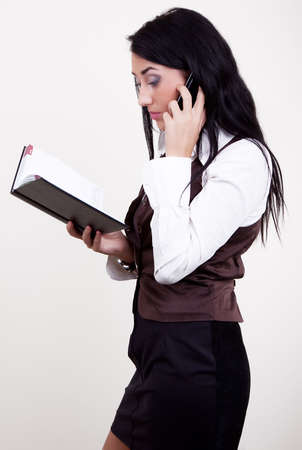 datebook: Attractive young businesswoman calling by mobile and looking in datebook.