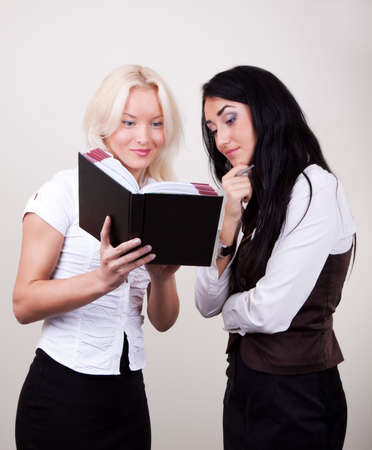 Portrait of two happy successful businesswomen in office, blonde and brunette. photo