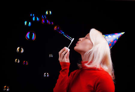 Attractive happy blonde blowing bubbles at party photo