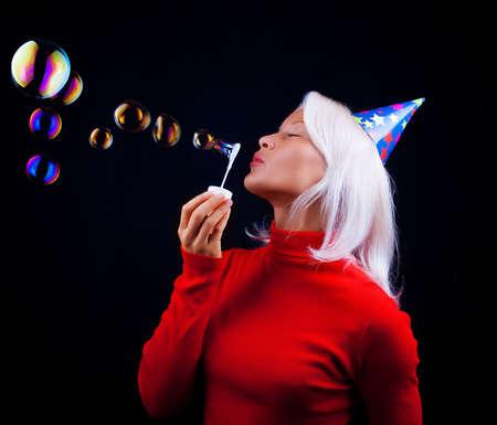 Attractive young woman blowing bubbles at party photo