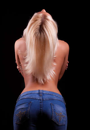 Portrait of young blonde in blue jeans from behind.