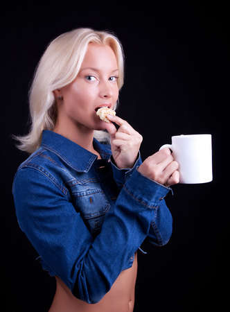Attractive blond girl eating cookie and drinking coffee Stock Photo - 5597601