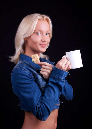 Portrait of attractive blond girl eating cookie and drinking coffee photo