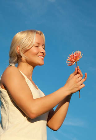 Portrait of attractive woman with beautiful flower in hands relaxing  in country photo