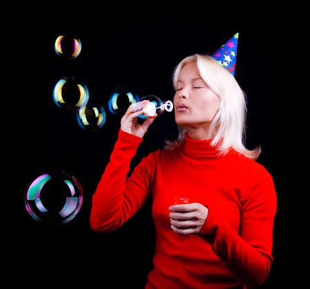 Attractive young blond woman blowing bubbles at party. Passion photo