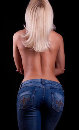 Portrait of young topless blonde in blue jeans from behind