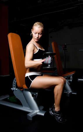 Portrait of a blond sportswoman lifting heavy dumbbells in empty dark gym room photo