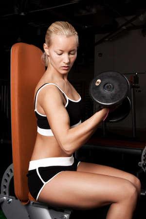 Portrait of a sportswoman lifting heavy dumbbells in dark gym room photo