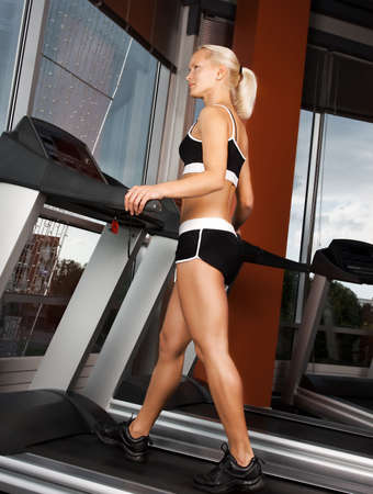 Portrait of young attractive athlete doing exercise on treadmill