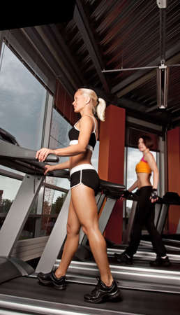 Portrait of two attractive girls doing exercise on treadmill photo