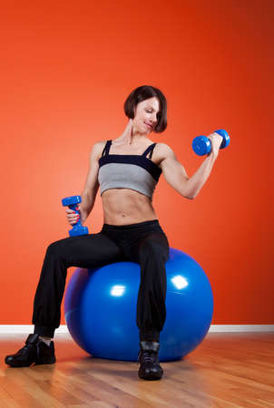 Portrait of athletic brunette with weights in gym photo